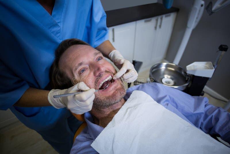 Tandläkare som undersöker en ung patient med hjälpmedel arkivfoto
