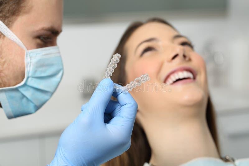 Tandläkare som visar en implantat till en patient royaltyfri foto