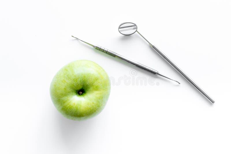 Tandläkarearbetsskrivbord med spegeln och äpplet på bästa sikt för vit bakgrund fotografering för bildbyråer