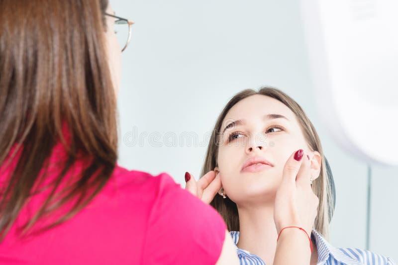 Tandläkarekvinnadoktor som talar till en ung patient som sitter på tandläkarestolen i ett medicinskt kontor Den första konversati royaltyfri fotografi