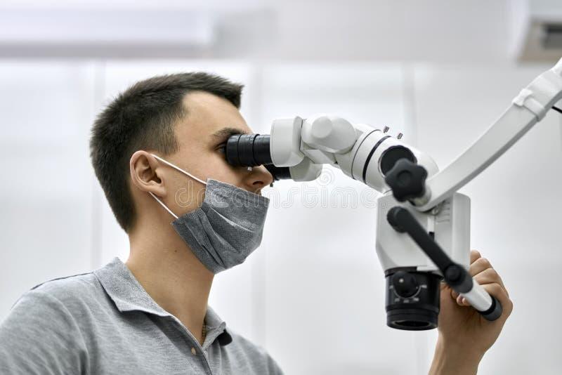 Tandläkaren använder det tand- mikroskopet under hans arbete royaltyfria foton
