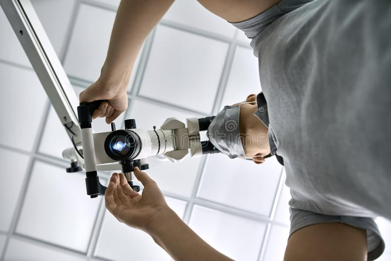 Tandläkaren använder det tand- mikroskopet under hans arbete royaltyfri bild