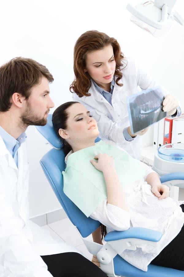 Tandläkaren förklarar detaljer av x-strålen fotografering för bildbyråer