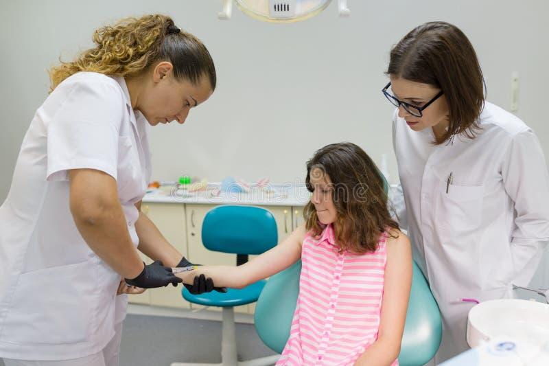 Tandläkaren gör en injektion i handen, kontrollerar reaktionen av kroppen till bedövande förberedelser royaltyfria foton