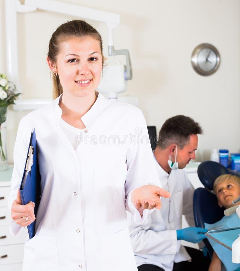 Tandläkaren som är assisstant i likformig, möter den nya klienten royaltyfria bilder