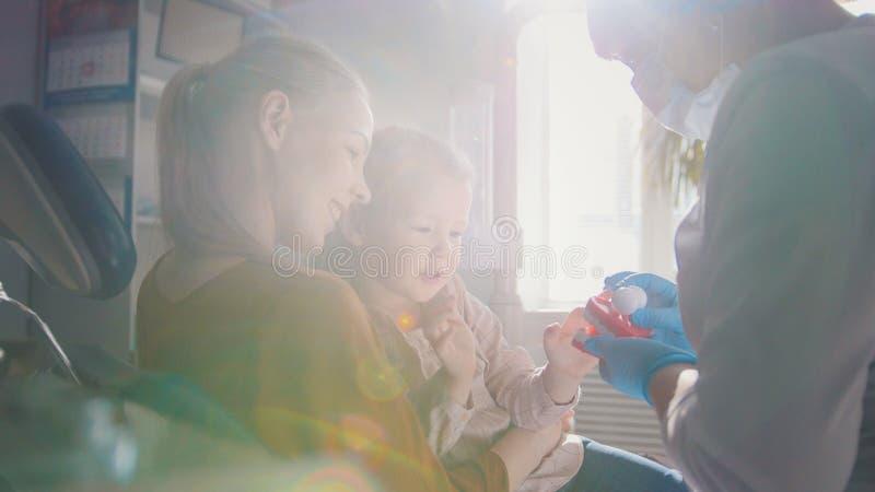 Tandläkaren som undersöker och konsulterar dottersammanträdet på hennes moder, knäa royaltyfria bilder