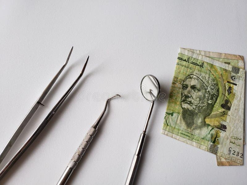 tandläkareredskap för muntlig granskning och den tunisian sedeln av fem dinar arkivbilder