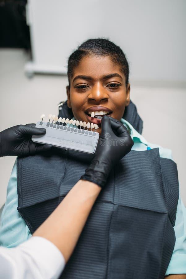 Tandl?kare som v?ljer skuggan av t?nder, tand- klinik fotografering för bildbyråer