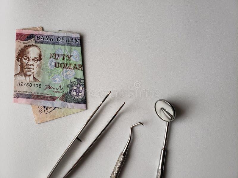 tandl?kareredskap f?r muntlig granskning och den jamaican sedeln av 50 dollar royaltyfri fotografi