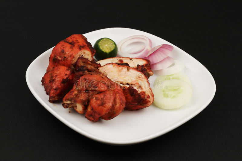 Tandoori chicken. A plate of chopped Tandoori chicken with some garnishing on a black background royalty free stock photography