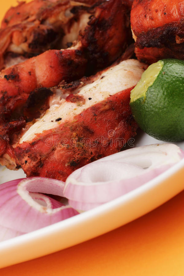 Tandoori chicken. Close-up of some chopped Tandoori chicken with garnishing by the side on an orange background royalty free stock photography