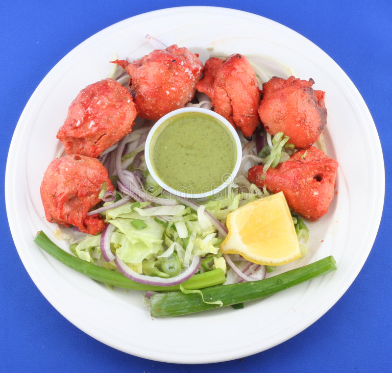 Tandoori chicken. Plate with tandoori chicken, vegetables and dipping royalty free stock images