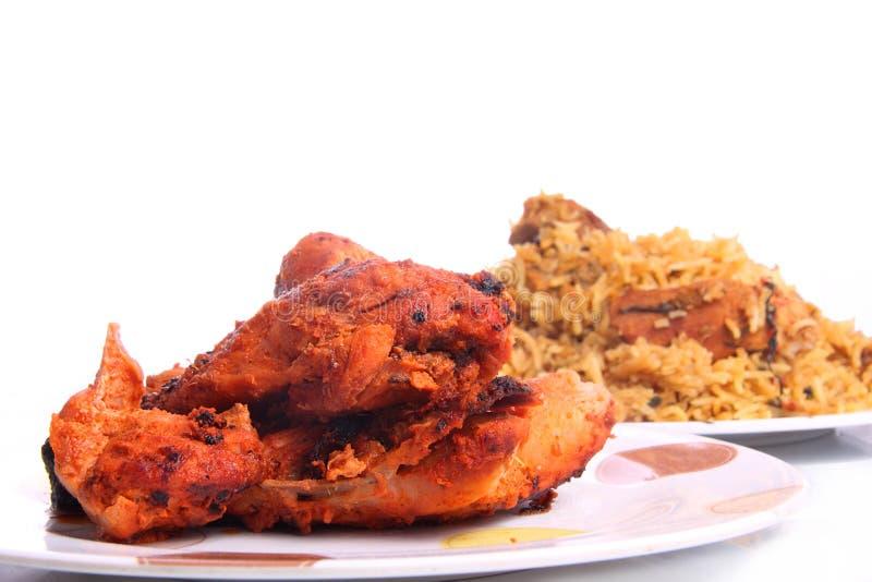 Tandoori chicken and chicken Biryani. Pieces of Tandoori chicken near chicken biryani, roasted leg piece and chicken wings are carefully kept near dum biryani stock image