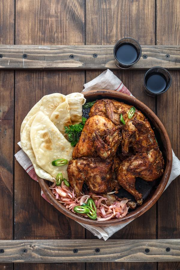 Tandoori chicken. Half of tandoori chicken served with lime slices and cilantro. Top view, blank space royalty free stock photography