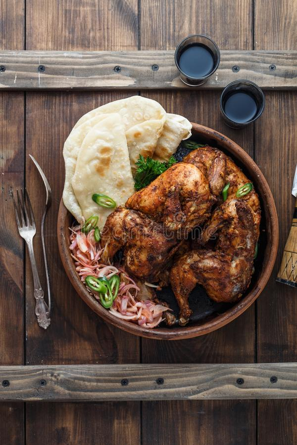 Tandoori chicken. Half of tandoori chicken served with lime slices and cilantro. Top view, blank space royalty free stock images