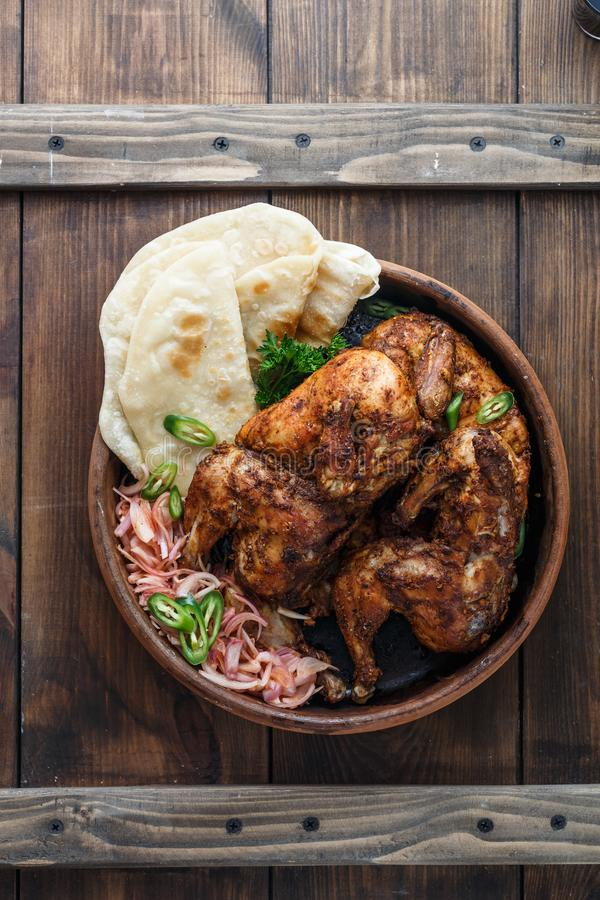 Tandoori chicken. Half of tandoori chicken served with lime slices and cilantro. Top view, blank space stock image