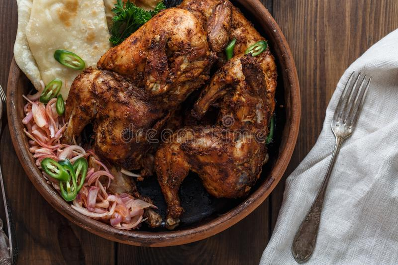 Tandoori chicken. Half of tandoori chicken served with lime slices and cilantro. Top view, blank space stock images