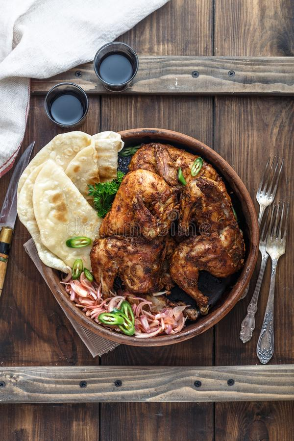 Tandoori chicken. Half of tandoori chicken served with lime slices and cilantro. Top view, blank space royalty free stock image