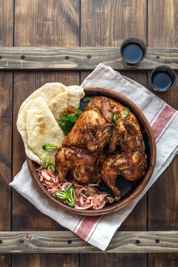 Tandoori chicken. Half of tandoori chicken served with lime slices and cilantro. Top view, blank space royalty free stock photo