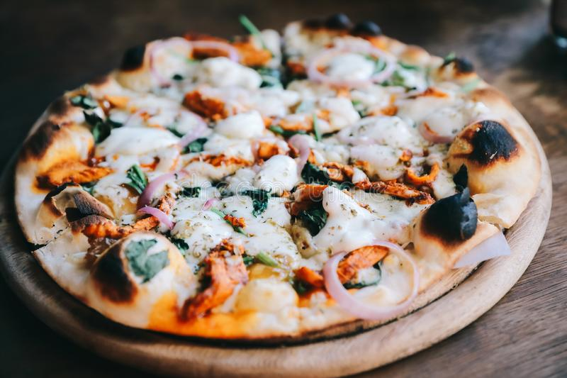Tandoori Chicken Pizza on wooden table. In close up stock image