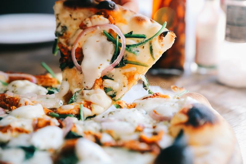 Tandoori Chicken Pizza on wooden table. In close up stock photography
