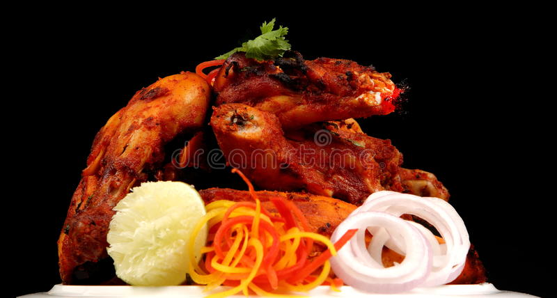 TANDOORI CHICKEN. Tandoor is a clay oven in which the spice and yogurt marinated chicken or meat is grilled and the chicken prepared in tandoori is a dish stock photo