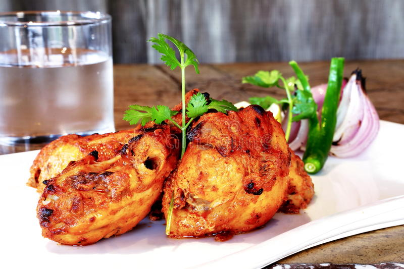 TANDOORI CHICKEN. Tandoor is a clay oven in which the spice and yogurt marinated chicken or meat is grilled and the chicken prepared in tandoori is a dish royalty free stock image
