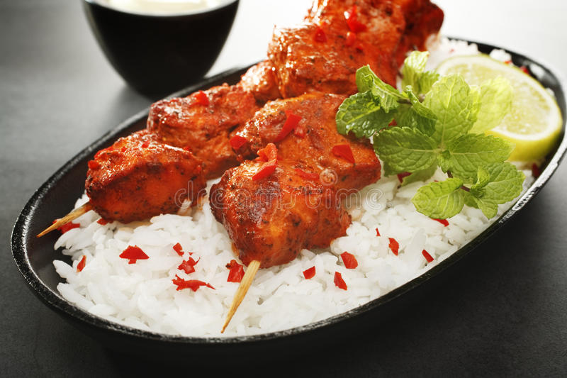 Tandoori Chicken Tikka with Rice. Tandoori chicken kebabs on a bed of rice, garnished with mint and lime, served with yoghurt, on a dark background royalty free stock photos