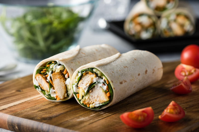 Tandoori chicken wrap with tzatziki. Fresh healthy chargrilled tandoori chicken wrap with tzatziki, cheese, baby spinach and carrots royalty free stock photos
