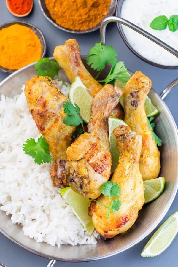 Tandoori indio del pollo, adobado en el yogur griego y las especias, servidos con las cuñas de la cal, cilantro y arroz basmati,  fotografía de archivo