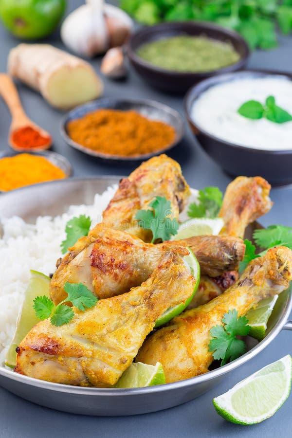 Tandoori indio del pollo, adobado en el yogur griego y las especias, servidos con las cuñas de la cal, cilantro y arroz basmati,  fotografía de archivo libre de regalías