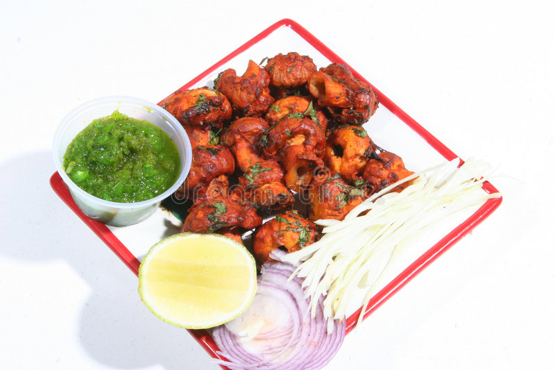 Tandoori mushrooms. Mushrooms roasted in a clay oven served in a plate with green chutney, onion and lime royalty free stock images