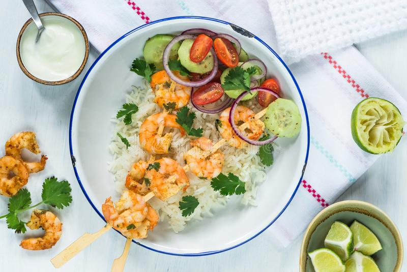 Tandoori prawn skewers with rice and chopped salad royalty free stock images