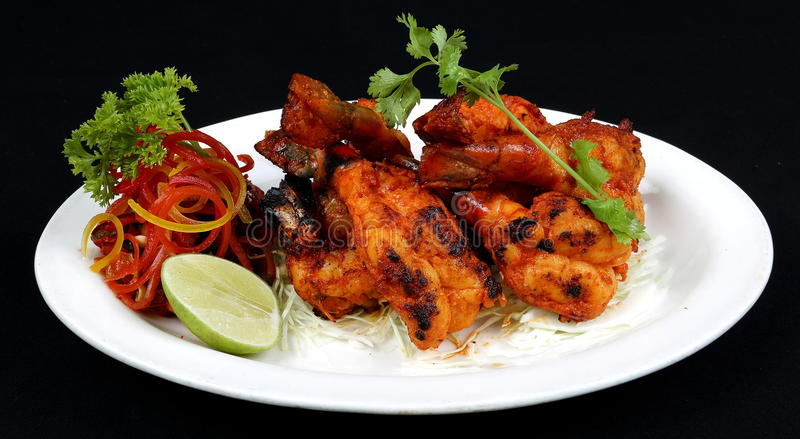 TANDOORI PRAWN. A tandoor is a cross between a barbecue pit and an oven. The waist-high, urn-shaped clay vessel holds a charcoal fire in the bottom. Seafood royalty free stock images