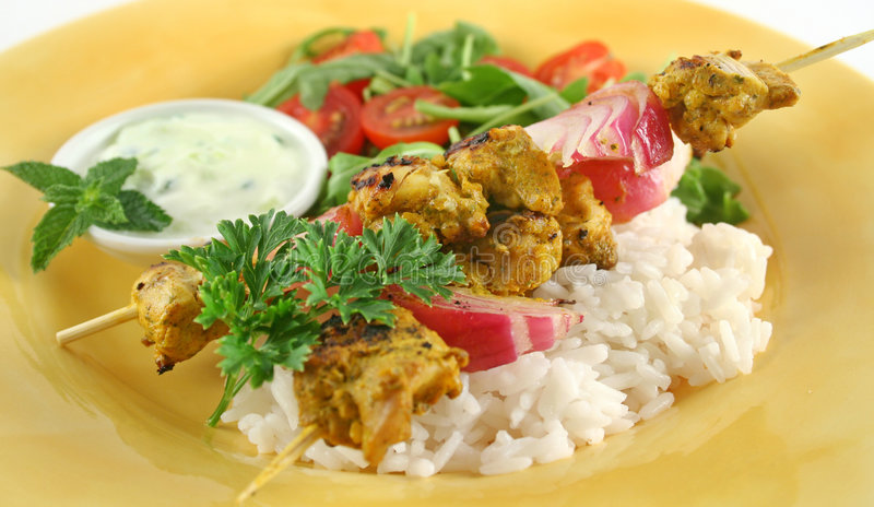Tandoorie Chicken Kabobs. Chicken tandoori skewers with minted yogurt and a rocket salad royalty free stock images