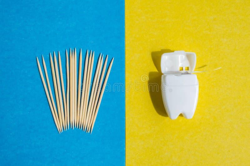 Tandpetare på blå bakgrund och tandtråd i den vita behållaren på den gula bakgrunden, bästa sikt royaltyfria foton