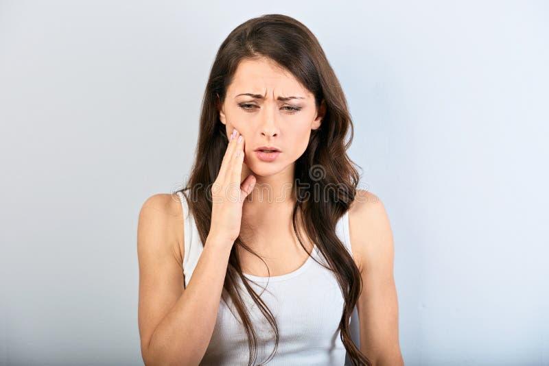 Tandpijn en Tandheelkunde Mooie jonge vrouw aan sterke tandenpijn lijden en de hand die wat betreft de wang Wijfje in toevallig royalty-vrije stock foto
