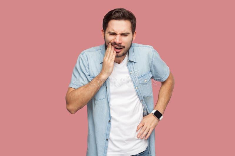 Tandpijn of pijn Portret van de droevige zieke gebaarde jonge mens in blauw toevallig stijloverhemd die en wat betreft zijn chik  royalty-vrije stock afbeelding