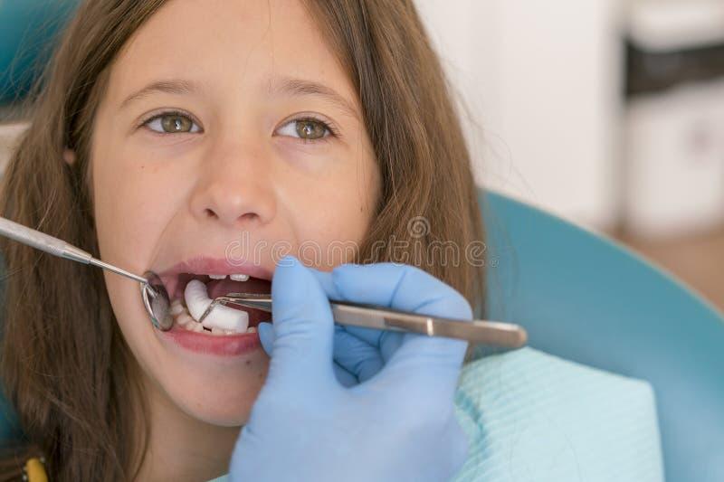 Tandundersökning på dentist& x27; s-kontor Liten flicka på mottagandet i dentist&en x27; s-kontor Liten flickasitts i arkivfoton