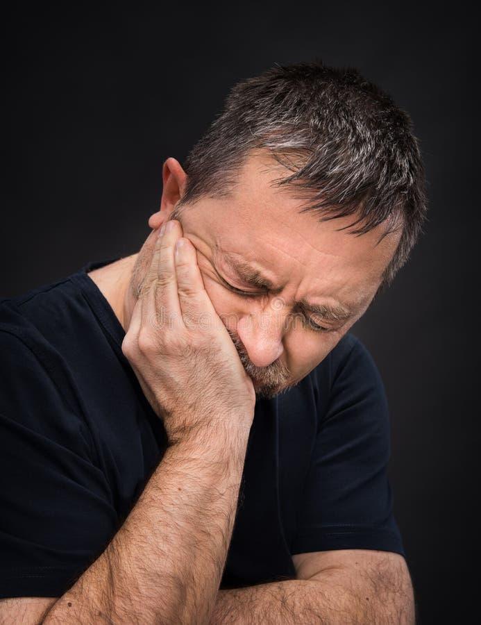 Tandvärk. Manen med vänder mot stängt räcker by arkivbild