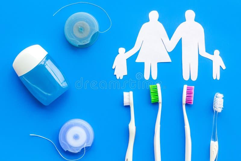Tandzorg met tandenborstel, tandzijde en familiecijfers Reeks van het schoonmaken van producten voor tanden op blauwe bovenkant a stock afbeeldingen