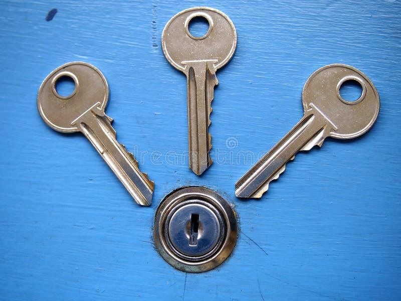 Tangenter och en nyckelhål på en blå dörr royaltyfri fotografi