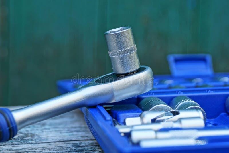 Tangentspärrhjul för grått järn med hålighethuvudet på den blåa asken med hjälpmedel arkivbild