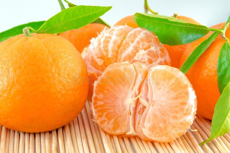 Tangerin eller clementine med det isolerade gröna bladet arkivfoto