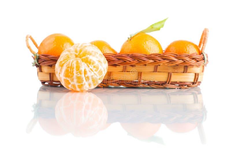 Tangerin i en korg på vit bakgrund arkivfoton