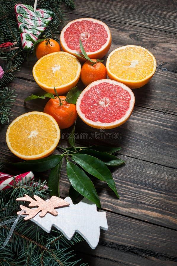 Tangerin med sidor i juldekor med julgranen, den torra apelsinen och godisar över den gamla trätabellen royaltyfri fotografi
