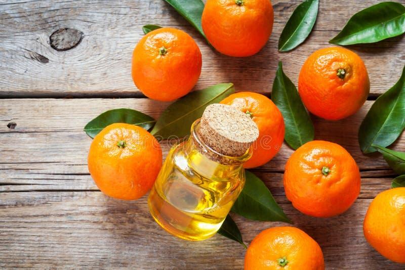 Tangerin med sidor och flaskan av den nödvändiga citruns oljer arkivfoto
