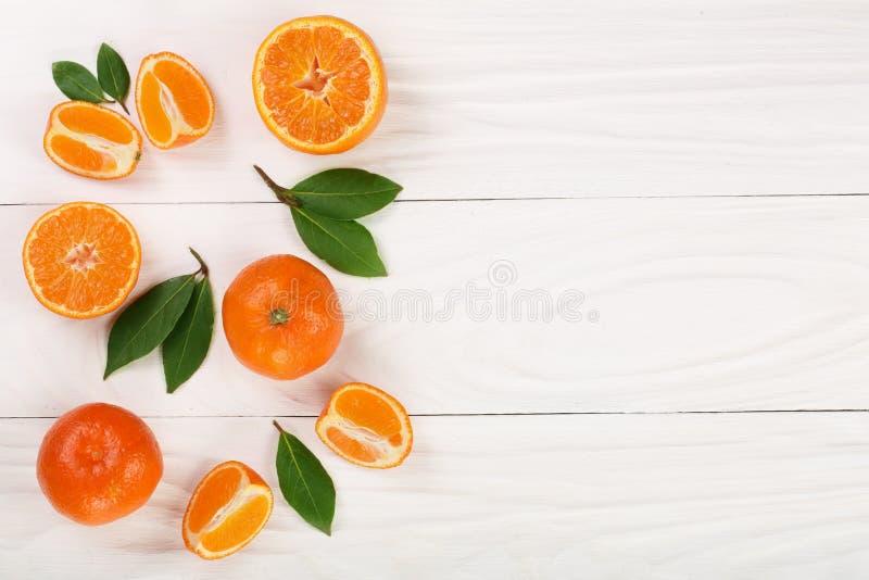 Tangerin med sidor på vit träbakgrund med kopieringsutrymme för din text Lekmanna- lägenhet, bästa sikt Isolerat på en vit bakgru fotografering för bildbyråer