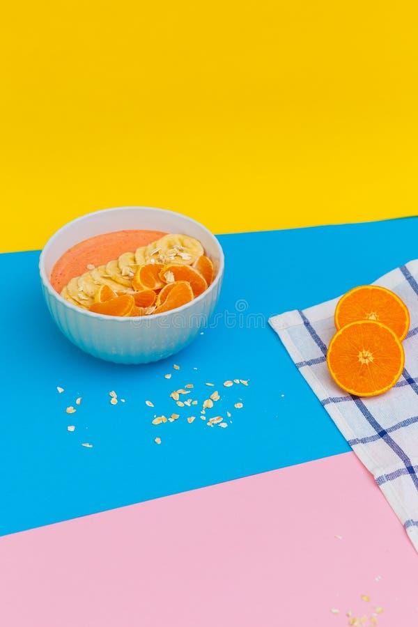 Tangerin och bananer p? en platta p? kul?ra bakgrunder r Top besk?dar arkivbild