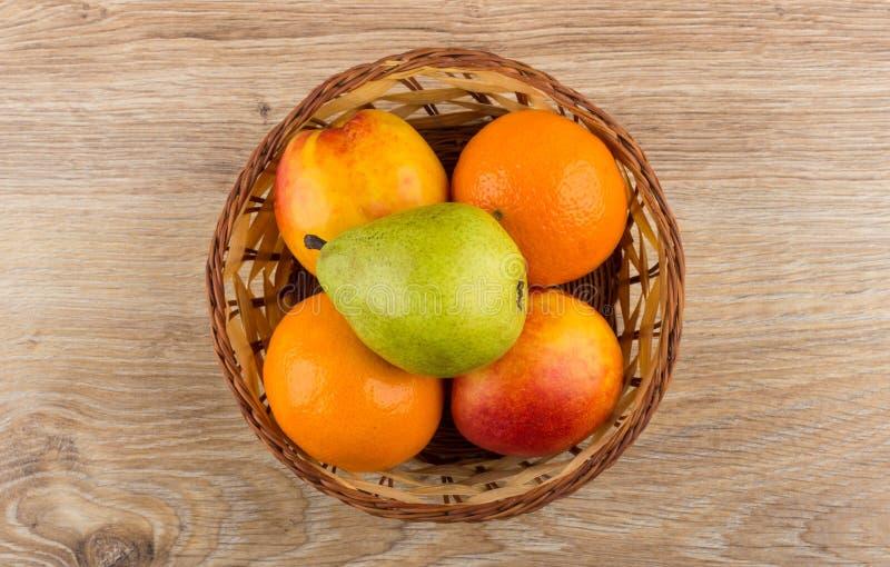 Tangerin, päron och nektariner i vide- korg på trätabl arkivfoton